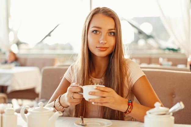 Hübsche frau, die tee in einem café an einem sonnigen sommertag trinkt.