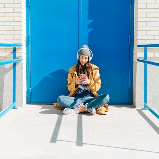 Hübsche frau, die tragenden kopfhörer des handys sitzt gegen blaue tür verwendet