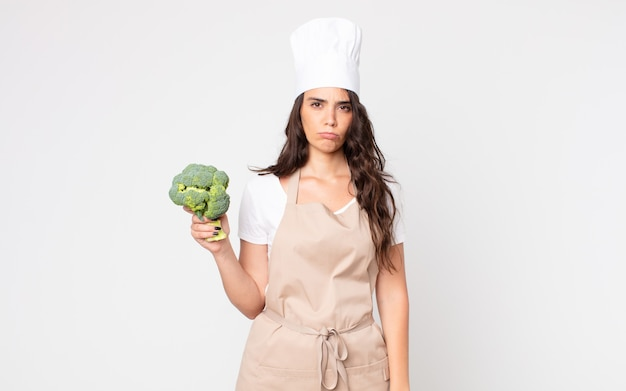 Hübsche frau, die traurig, verärgert oder wütend ist und zur seite schaut, eine schürze trägt und einen brokkoli hält