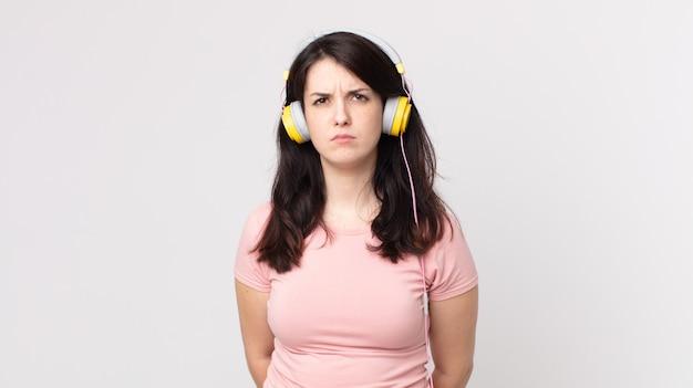 Hübsche frau, die traurig, verärgert oder wütend ist und zur seite schaut und musik mit kopfhörern hört