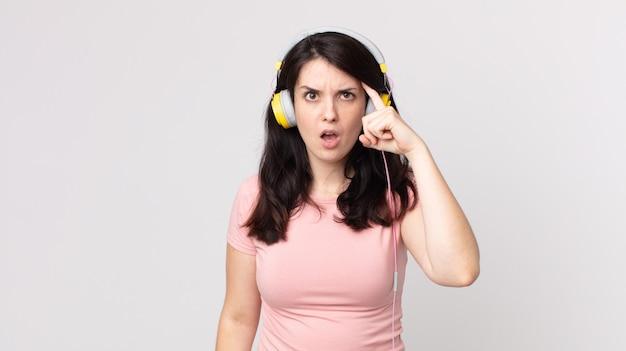 Hübsche frau, die überrascht aussieht und einen neuen gedanken, eine neue idee oder ein neues konzept realisiert, das musik mit kopfhörern hört