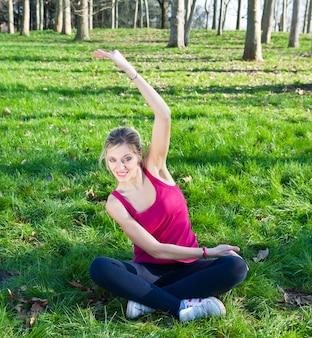 Hübsche frau, die übungen im park tut