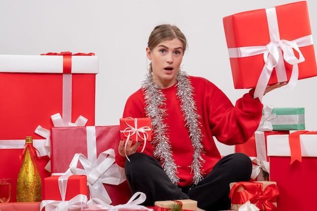 Hübsche frau, die um weihnachtsgeschenke auf weiß sitzt