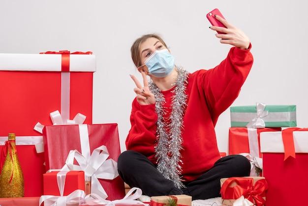 Hübsche frau, die um weihnachtsgeschenke herum sitzt und selfie auf weiß nimmt