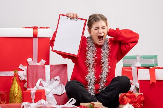 Hübsche frau, die um weihnachtsgeschenke mit anmerkung auf weiß sitzt