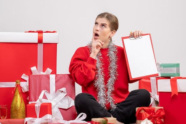 Hübsche frau, die um weihnachtsgeschenke mit notiz sitzt, die auf weiß denkt