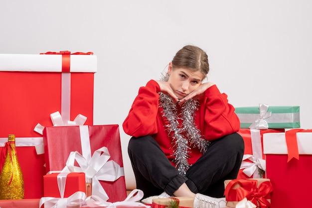 Hübsche frau, die um weihnachtsgeschenke sitzt, betont auf weiß