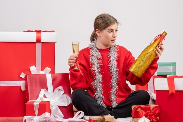 Hübsche frau, die um weihnachtsgeschenke sitzt, die mit champagner auf weiß feiern