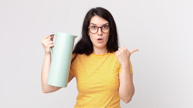 Hübsche frau, die ungläubig ausschaut und eine kaffeethermos hält