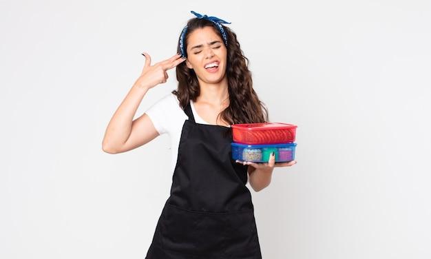 Hübsche frau, die unglücklich und gestresst aussieht, selbstmordgeste, die waffenzeichen macht und tupperware mit essen hält