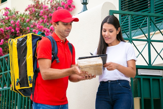 Hübsche frau, die unterschrift in zwischenablage und kurierhaltebox setzt. brünette kundin, die die lieferung des pakets vom zusteller in der roten uniform annimmt. hauslieferdienst und postkonzept