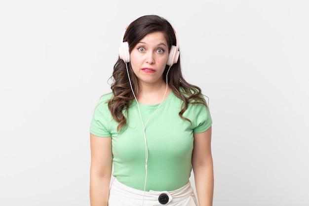 Hübsche frau, die verwirrt und verwirrt aussieht und musik mit kopfhörern hört