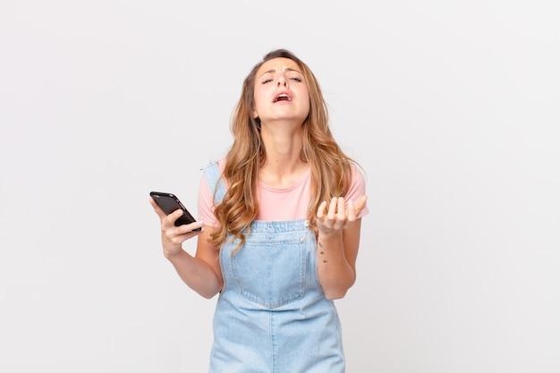 Hübsche frau, die verzweifelt, frustriert und gestresst aussieht und ein smartphone hält