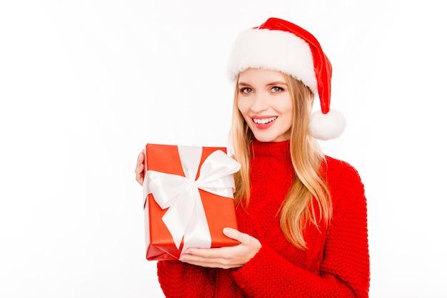 Hübsche frau, die weihnachtsmütze trägt, die geschenk zeigt