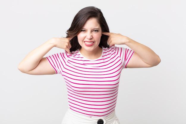 Hübsche frau, die wütend, gestresst und verärgert aussieht und beide ohren zu einem ohrenbetäubenden geräusch, ton oder lauter musik bedeckt
