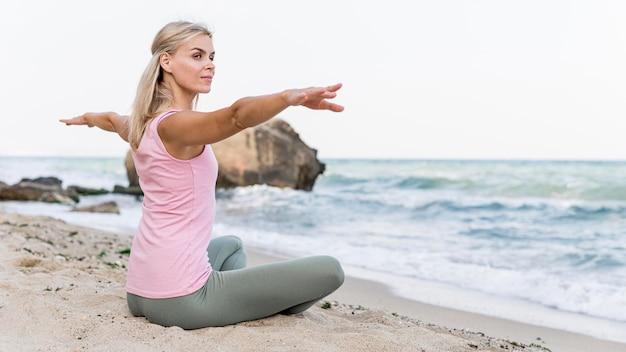 Hübsche frau, die yoga am strand praktiziert