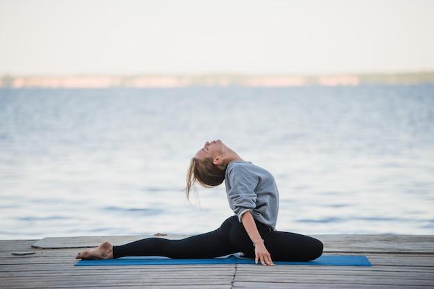 Hübsche frau, die yoga an einem see praktiziert