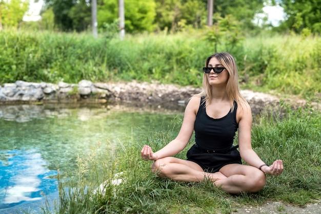 Hübsche frau, die yoga meditation nahe see, im freien tut