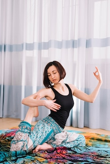 Hübsche frau, die yoga mit mudra geste in der eignungsmitte tut