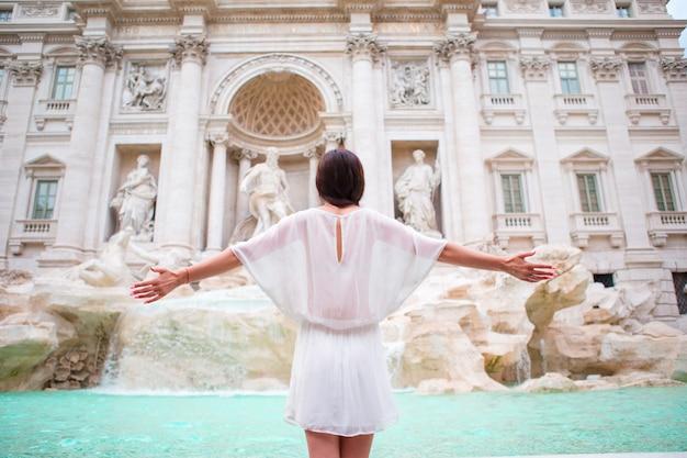 Hübsche frau, die zum brunnen von trevi während ihrer reise in rom, italien schaut. mädchen genießen ihre europäischen ferien