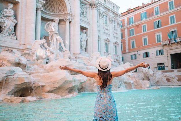 Hübsche frau, die zum brunnen von trevi während ihrer reise in rom, italien schaut,