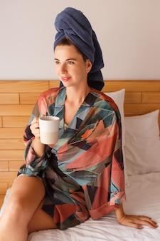 Hübsche frau, eingewickelt in handtuch und bademantel, die am morgen auf dem bett sitzend aufwacht und tee trinkt