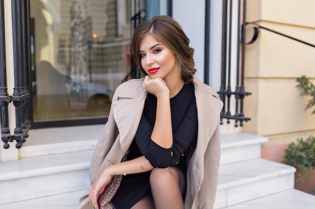 Hübsche frau gekleidet in schwarzem kleid und beigem trenchcoat mit stilvoller frisur und roten lippen auf der straße