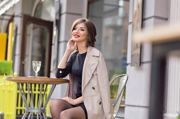 Hübsche frau gekleidet in schwarzem kleid und beigem trenchcoat mit stilvoller frisur und roten lippen auf einer terrasse