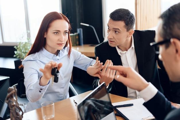 Hübsche frau hält an fingerschlüssel im büro