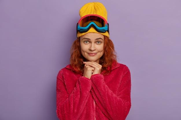 Hübsche frau hat hände zusammen, trägt gelben hut und roten mantel, schaut direkt in die kamera, hat grübchen auf den wangen. aktiver skifahrer