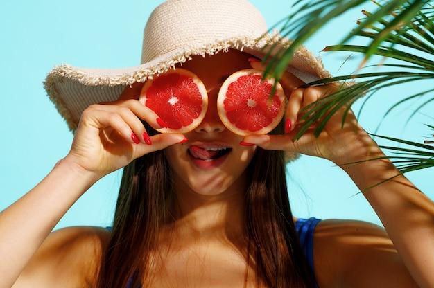 Hübsche frau im badeanzug wirft mit früchten auf blau auf