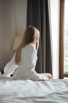 Hübsche frau im bademantel, die auf bett im hotel sitzt