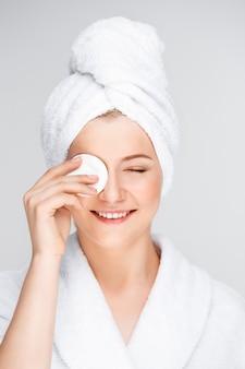Hübsche frau im bademantel-make-up mit reinigungsmittel