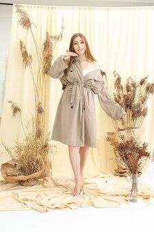 Hübsche frau im beigen regenmantel auf pastellfarbenem stoffhintergrund. mode-fotoshooting
