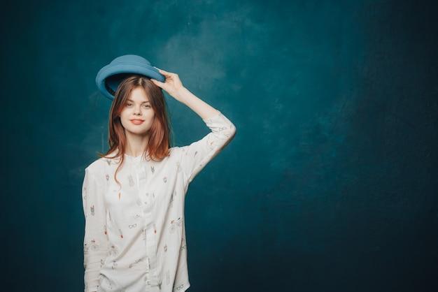 Hübsche frau im blauen hut zeigt mit ihrer hand zur seite auf einem dunklen wandkopierraum
