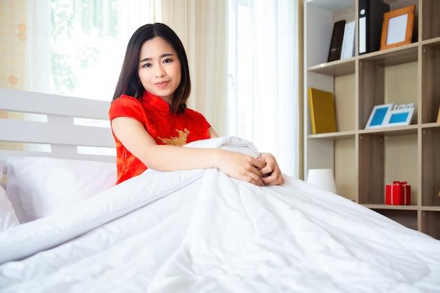 Hübsche frau im chinesischen kleid im schlafzimmer