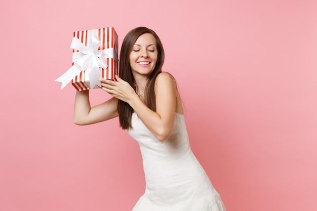 Hübsche frau im eleganten weißen kleid, die versucht zu erraten, was in der roten schachtel mit geschenk ist, geschenk