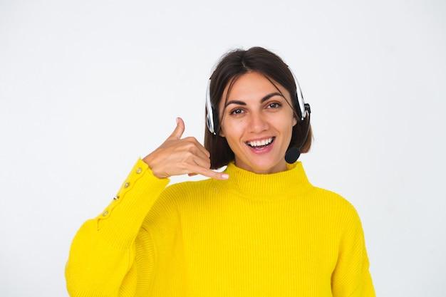Hübsche frau im gelben pullover auf weißem manager mit kopfhörern glücklicher positiver telefongeste