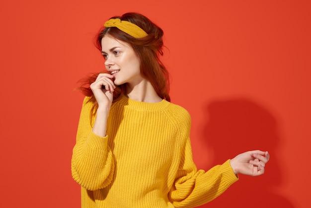 Hübsche frau im gelben pullover, die ihre kopfgefühle hippie-mode hält