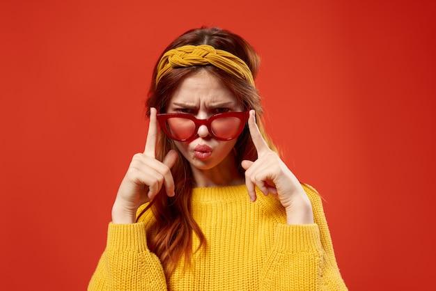 Hübsche frau im gelben pullover mit roten brillen studiomode posiert