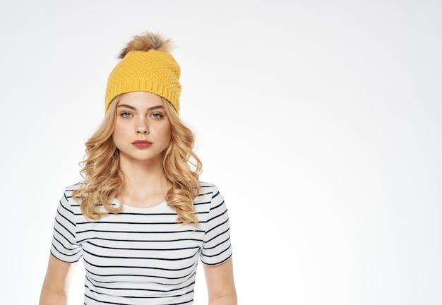 Hübsche frau im gestreiften gelben t-shirthut