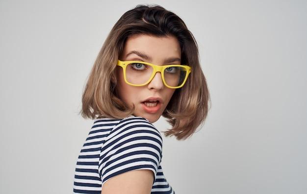 Hübsche frau im gestreiften grauen modell der gelben brille gestreifte t-shirt