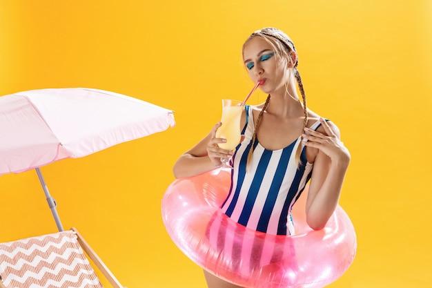 Hübsche frau im gestreiften strandoutfit trinkt cocktail nach dem schwimmen