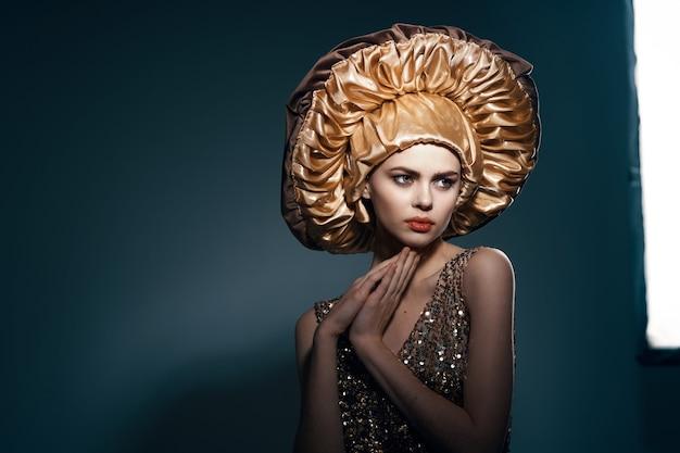 Hübsche frau im großen goldenen hut vintage lifestyle glamour