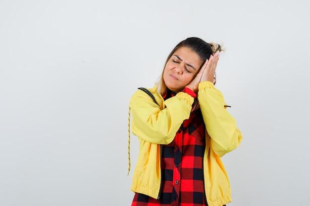 Hübsche frau im hemd, jacke, die sich auf palmen als kissen stützt und schläfrig aussieht, vorderansicht.