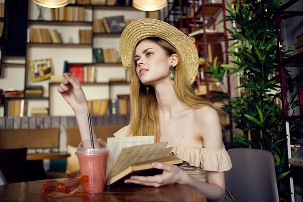 Hübsche frau im hut mit buch in den händen, die urlaub im café lesen.