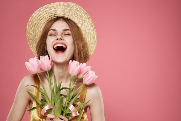 Hübsche frau im hutstrauß blüht feiertagsgeschenk rosa hintergrund
