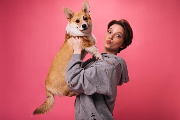 Hübsche frau im kapuzenpulli hält hund auf rosa hintergrund. charmante dunkelhaarige dame im grauen outfit spielt mit corgi auf isoliert
