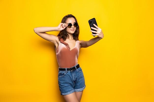 Hübsche frau im kleid, das selfie lokalisiert über gelb macht