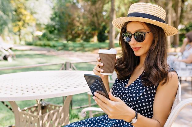 Hübsche frau im kleid, im sommerhut und in der sonnenbrille sitzt in der sommercafeteria und ruht sich aus. sie trinkt kaffee und schaut mit einem leichten lächeln in ihr handy. schönes porträt. platz für text.